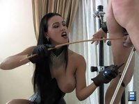 Cruel Cane: Mistress Megan has her slave bent over and locked down with his balls restrained behind his back.